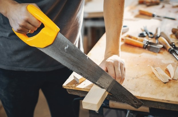 a man working with hand saw