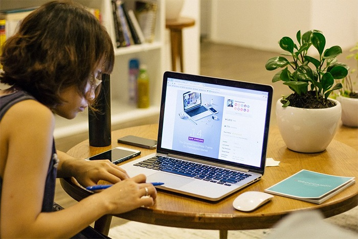 a woman facing her laptop, a woman working on a table, busy woman, a woman in a small room